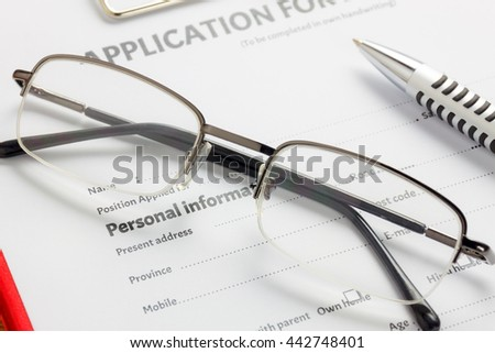Business document concept the pen,eyeglasses on business document application form. - stock photo