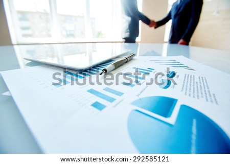 Business document, pen and digital tablet at workplace with handshaking partners on background - stock photo
