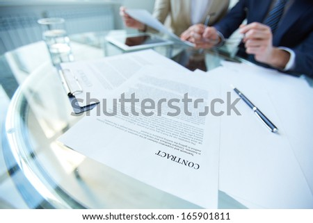 Business documents and pen at workplace with working people on background - stock photo