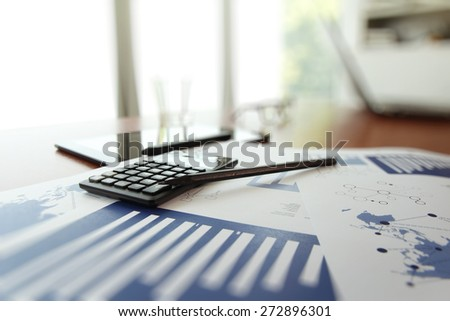 business documents on office table with calculator and digital tablet as work space business concept - stock photo