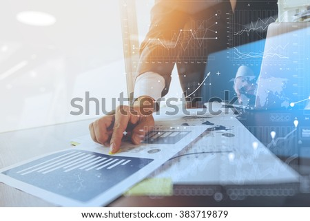 business documents on office table with laptop computer and graph financial with social network diagram and man working in the background - stock photo