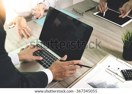 business documents on office table with smart phone and blank screen laptop computer and graph business diagram and three colleagues discussing data in the background - stock photo