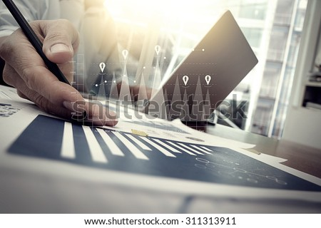 business documents on office table with smart phone and digital tablet and graph business with social network diagram and man working in the background - stock photo
