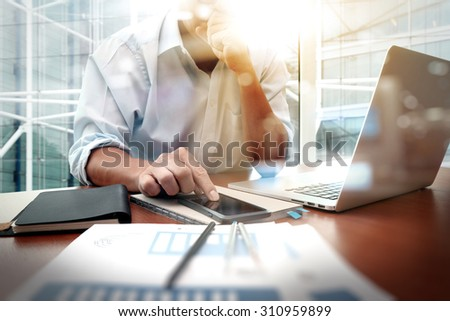 business documents on office table with smart phone and digital tablet and graph financial diagram and man working in the background - stock photo
