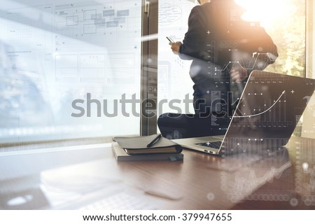 business documents on office table with smart phone and digital tablet and graph financial with social network diagram and man working in the background - stock photo