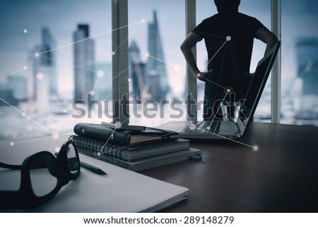business documents on office table with smart phone and digital tablet and london city blurred view and man thinking in the background and social network diagram