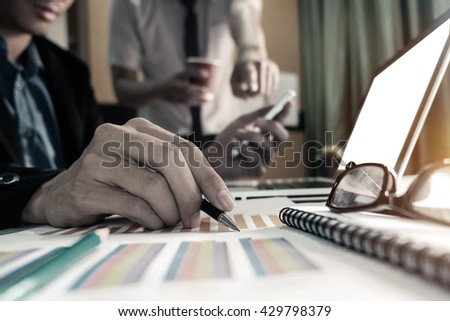 business documents on office table with smart phone and laptop and two colleagues discussing data in the black and white background  - stock photo