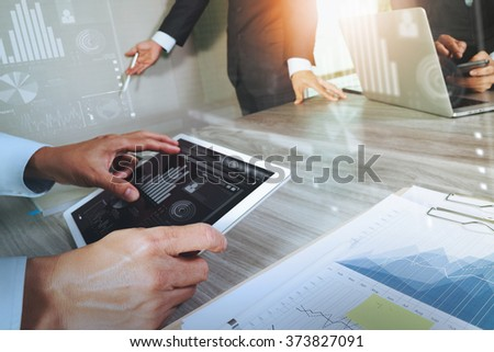 business documents on office table with smart phone and laptop computer and digital graph business with social network diagram and three colleagues discussing data in the background - stock photo