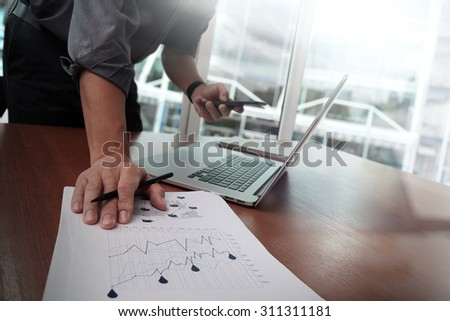business documents on office table with smart phone and laptop computer and graph business with social network diagram and man working in the background - stock photo