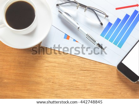 Business documents the Mobile phone or smartphone eyeglasses,pen,coffee on business chart background.Chart on wood table. - stock photo