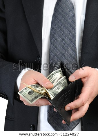 Business dressed man counting US dollars in his leather wallet - stock photo