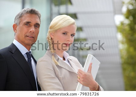 Business duo outside with a laptop - stock photo