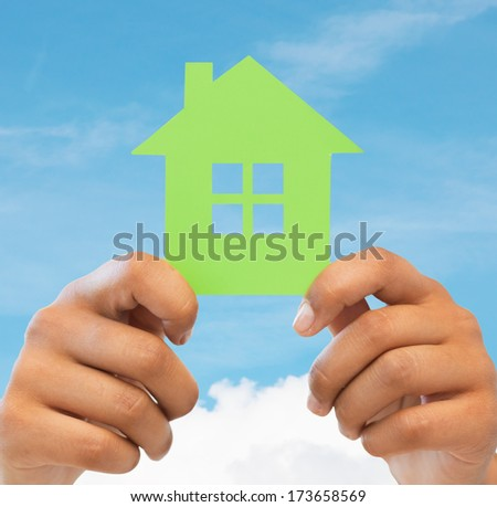 business, eco and real estate concept - closeup picture of woman hands holding green house - stock photo