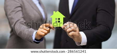 business, eco, real estate and office concept - businessman and businesswoman holding green house in office - stock photo
