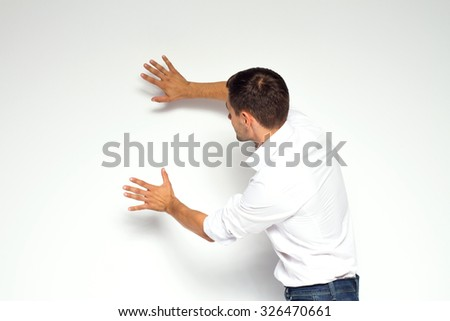 Business, education and office concept - businessman or teacher touching or moving on something from back on white background - stock photo