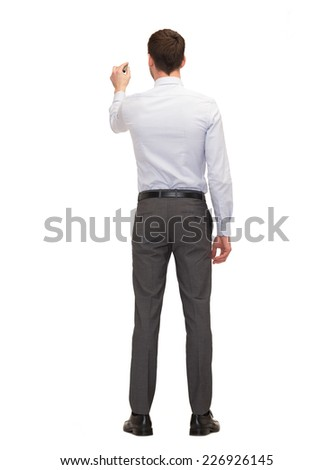 business, education and office concept - businessman or teacher with marker writing or drawing something imaginary from back