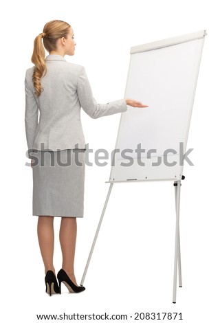 business, education and office concept - businesswoman or teacher showing something imaginary on whiteboard from back - stock photo