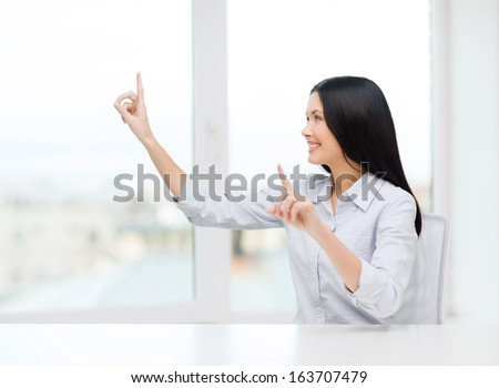 business, education and technology concept - smiling woman pointing to something or pressing imaginary button - stock photo