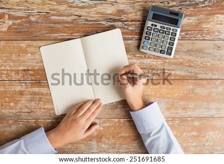 business, education, people and technology concept - close up of female hands with calculator, pen and notebook on table - stock photo