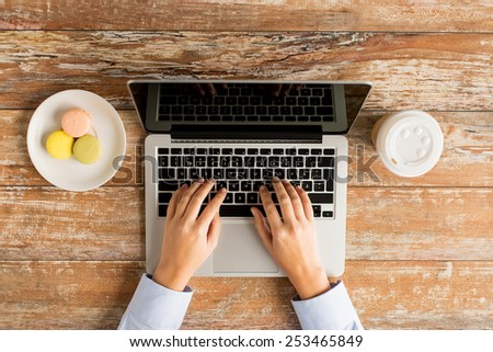 business, education, people and technology concept - close up of female hands with laptop computer, cookies and coffee cup on table - stock photo