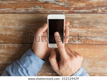 business, education, people and technology concept - close up of male hands holding smartphone and pointing finger to screen on table - stock photo