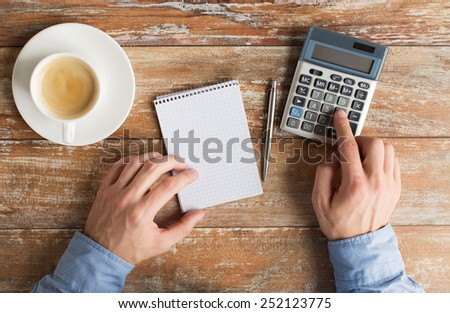business, education, people and technology concept - close up of male hands with calculator, pen and notebook on table - stock photo