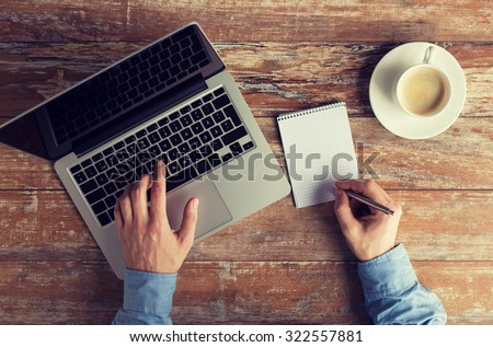 business, education, people and technology concept - close up of male hands with laptop and coffee cup taking notes to notebook by pen - stock photo