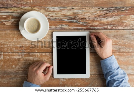 business, education, people and technology concept - close up of male hands with tablet pc computer and coffee cup on table - stock photo