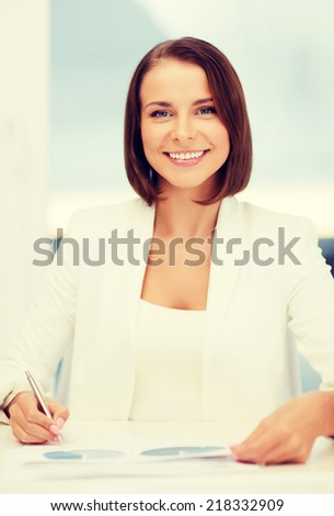 business, education, people concept - businesswoman or student working with graphs in office