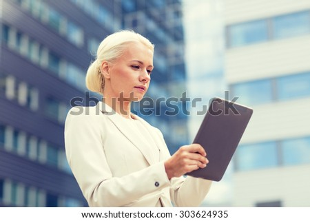 business, education, technology and people concept - businesswoman working with tablet pc computer on city street