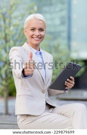 business, education, technology, gesture and people concept - smiling businesswoman working with tablet pc computer showing thumbs up on city street - stock photo