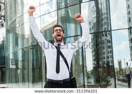 Business excitement. Cheerful young businessman keeping arms raised and expressing positivity while standing outdoors