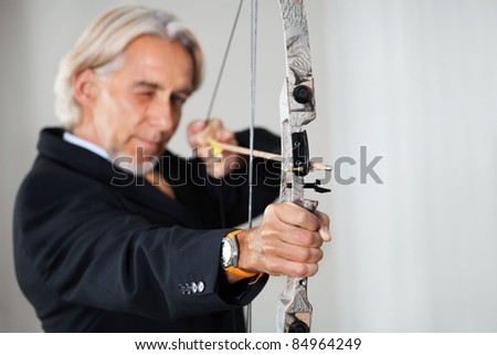 Business executive aiming at target - stock photo