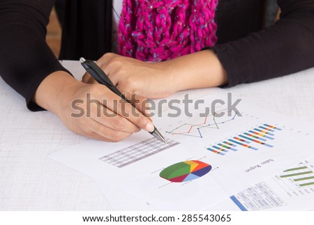 Business executive analyzing sales report with charts and graphs. Person wearing business casual wear in her office room. Concept for woman in business. - stock photo
