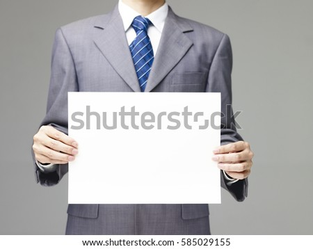 business executive in suit holding a piece of blank white paper, gray background.
