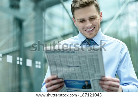 Business executive reading newspaper and smiling - stock photo