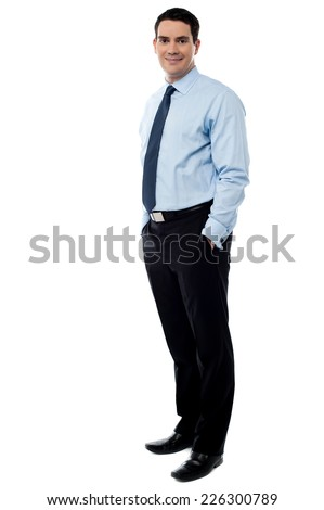 Business executive standing with his hands in pockets - stock photo