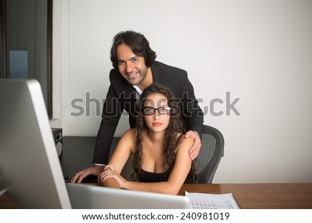 Business executives at the office working looking at the camera - stock photo