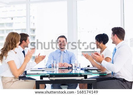Business executives clapping around conference table in a bright office - stock photo
