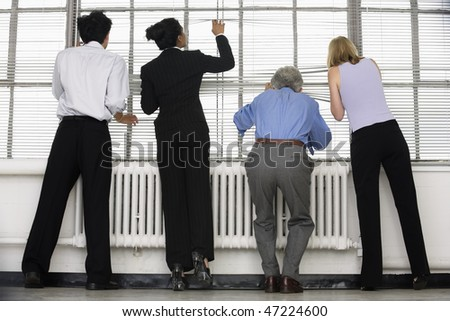 Business executives looking through blinds. - stock photo