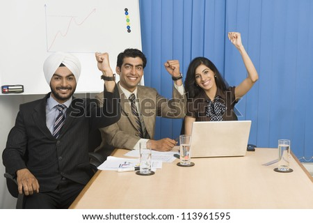 Business executives raising hands in an office - stock photo