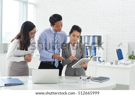 Business executives reading information in notepad