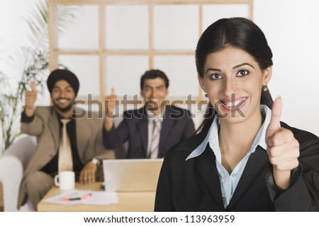 Business executives showing thumbs up sign - stock photo
