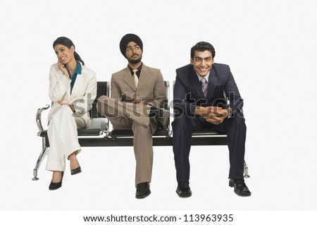 Business executives sitting on a bench - stock photo