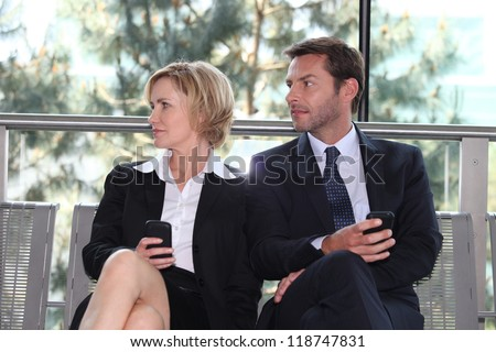 Business executives sitting on a bench texting - stock photo