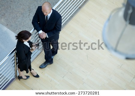 Business executives standing together while businesswoman using mobile phone - stock photo