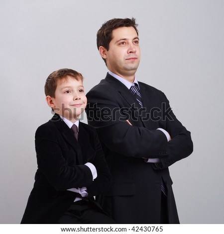 Business family. Father and son in suit on a gray background. - stock photo