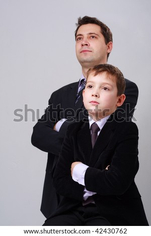 Business family. Father and son on a gray background. - stock photo