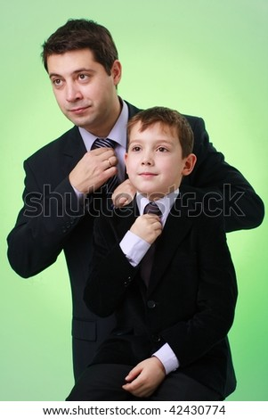Business family. Father and son on a green background. - stock photo