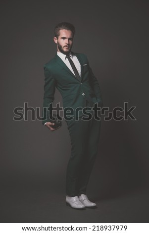 Business fashion man wearing green suit with white shirt and black tie. Holding vintage camera. Studio shot against grey.